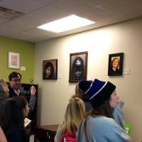Crowd admiring art in the women's center